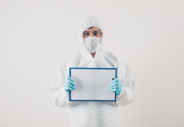 医療用手袋と防護服の明るい背景でホワイトボードを保持している医師。コロナウイルス