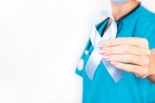 医者は彼女のtシャツの背景に青いリボンを持っています