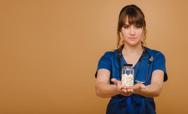 青い白衣を着た医師が茶色の壁にカプセルの瓶を手に持っています