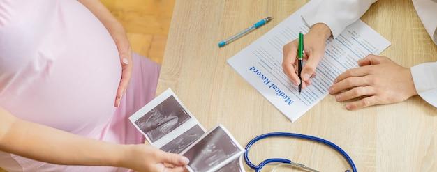 Врач в поликлинике осматривает беременную женщину