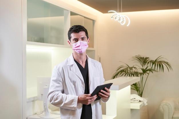 Врач в маске смотрит в камеру с планшетом в руке. гинекологическая, стоматологическая или эстетическая клиника. медицинская концепция.
