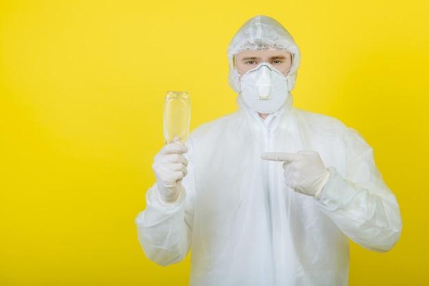 Врач в индивидуальном защитном костюме (сиз) держит в руках флакон с дезинфицирующим средством, носит медицинскую маску и перчатки. изолированные. желтый фон