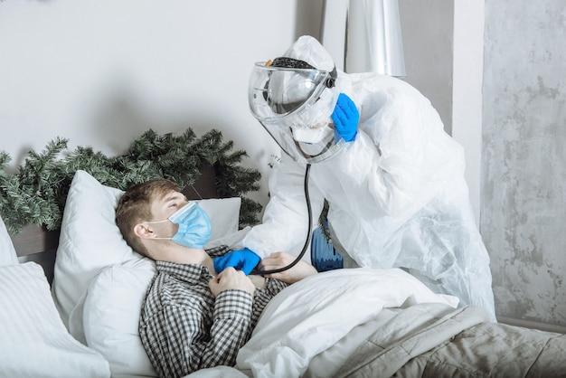 Ppe防護服、マスク、手袋、眼鏡をかけた医師がcovid-19の間に聴診器で患者の話を聞きます