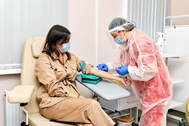Врач в защитной форме и маске вакцинирует женщину в поликлинике.
