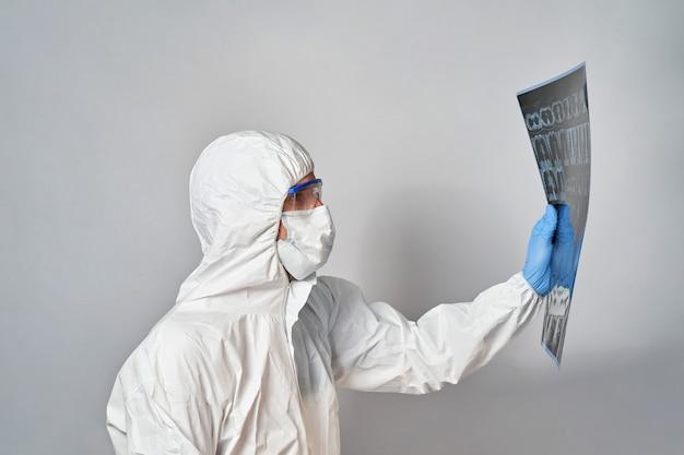 보호 복과 마스크를 착용 한 의사가 폐 ct 스캔 결과를보고 코로나 바이러스를 감지합니다.