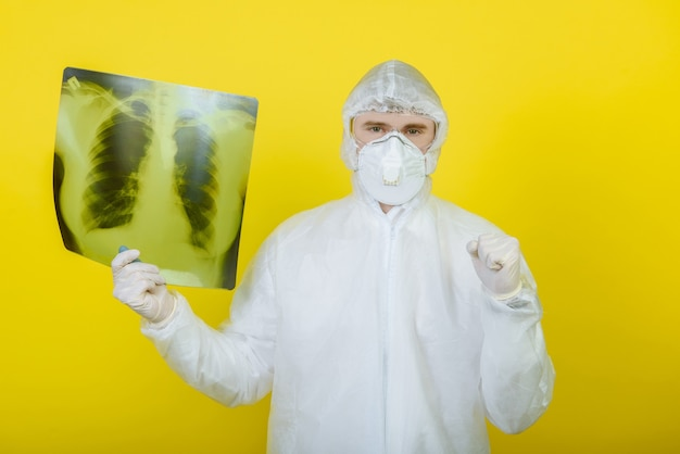 肺のx線写真を持った防護服を着た医師が、スタジオの黄色い背景に手を置いて承認のサインを示しています。コロナウイルスcovid-19の概念。