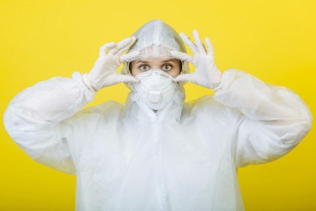 個人用保護具(ppe)のスーツを着た医師が、黄色の背景に眼鏡をかけています。コロナウイルス