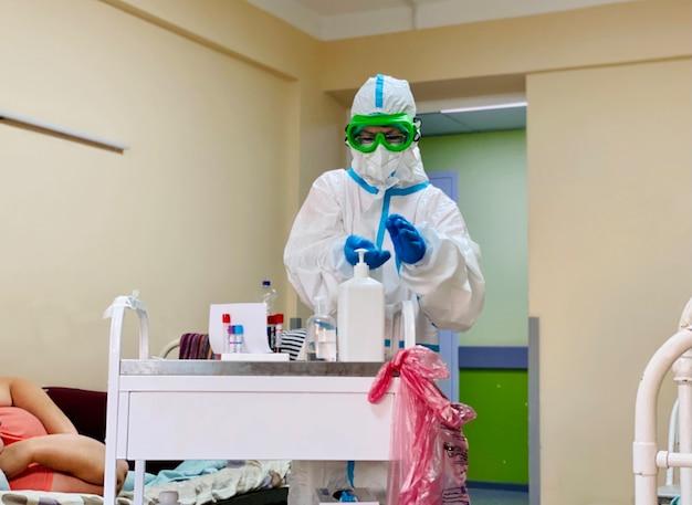 Врач в противочумном костюме сдает анализы крови у пациента с коронавирусом