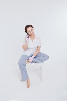 手袋をはめた医師が電話で話している女性は事業計画、検疫、自己隔離、コロナウイルスからの保護、ウイルス、遠隔作業のテクニックを学びます。