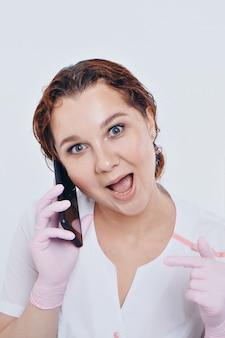 手袋をした医師が白い背景に電話で話しています。