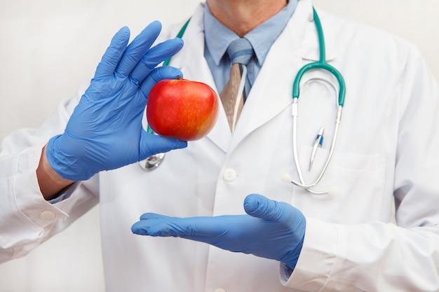 보호 장갑을 입은 의사가 사과를 보여줍니다.