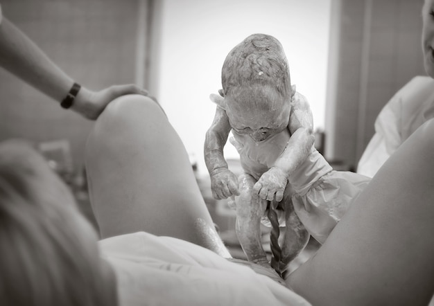 Врач в больнице держит новорожденного ребенка, черно-белое фото, врач показывает новорожденного матери.