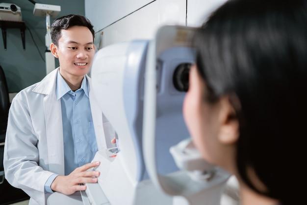 Врач осматривает пациентку с помощью глазного компьютера в офтальмологической клинике
