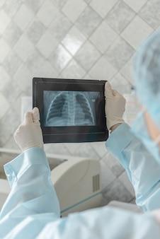 医師は、コロナウイルス病の患者のフルオログラフィースキャンを見ています。