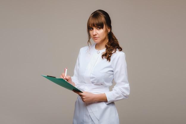 Врач на сером фоне с медицинским заключением в руках и что-то пишет