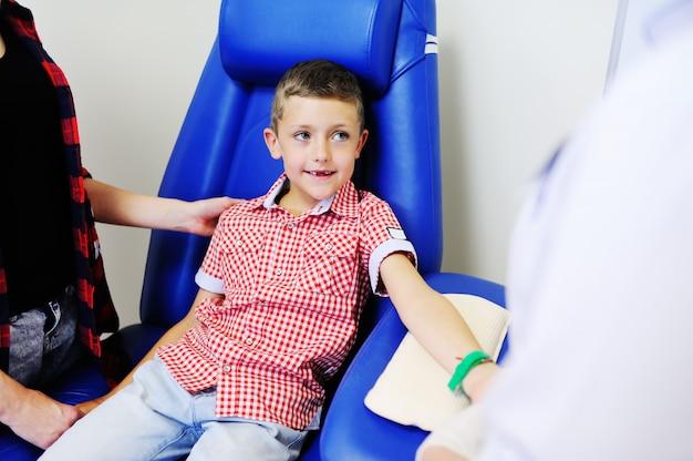 Врач или медсестра берут кровь из вены у ребенка мальчика. химия крови