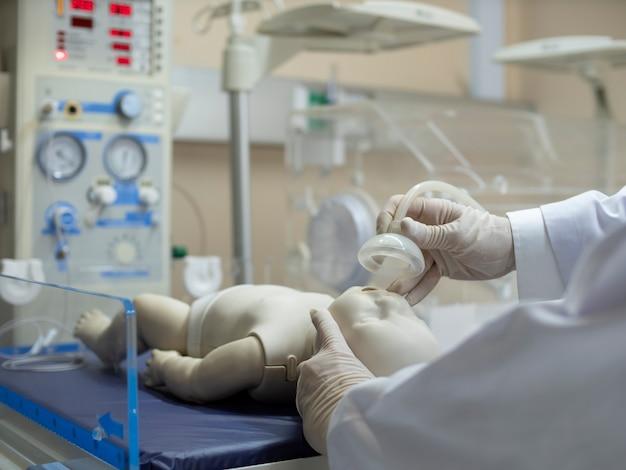 신생아에게 산소 마스크를 착용하는 의사