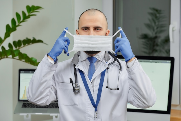 医師が自分のオフィスでコロナウイルス(covid-19)の蔓延を防ぐために防護マスクを着用している。