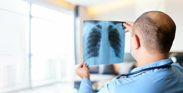의사가 밝은 병원의 대기실에서 흉부 x- 레이를 읽습니다.