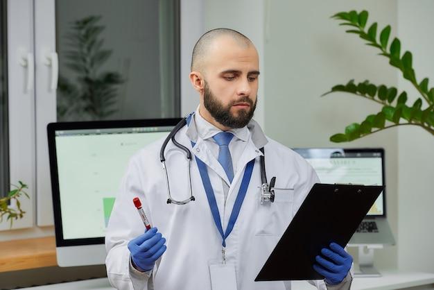 Врач исследует исследование трубки крови коронавируса (covid-19) в лаборатории.