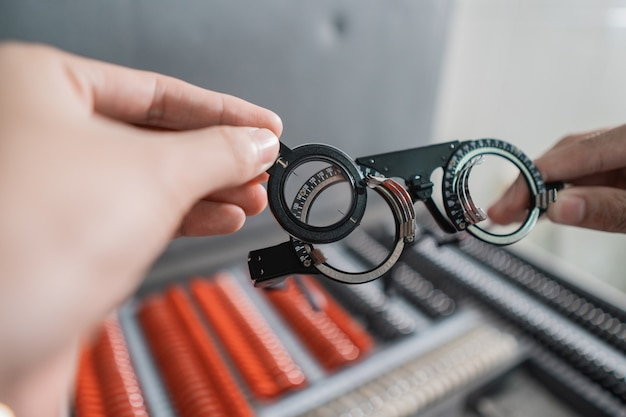 Рука врача держит экспериментальную оправу линзы в комнате офтальмологической клиники на фоне коробки оправы очков.