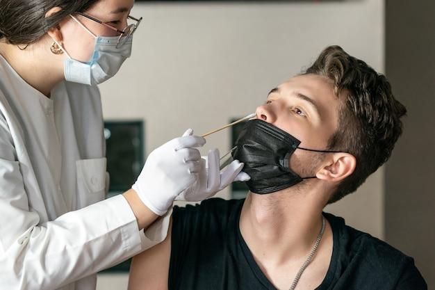 의사는 젊은 남자의 코 dna 검사 pcr 검사에서 면봉을 가져옵니다.