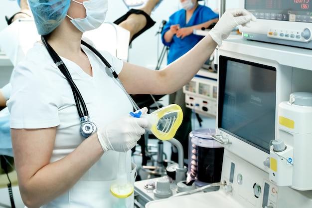 マスクと手袋を着用した医師が、コロナウイルス患者の肺を人工呼吸するための蘇生装置を準備しています。