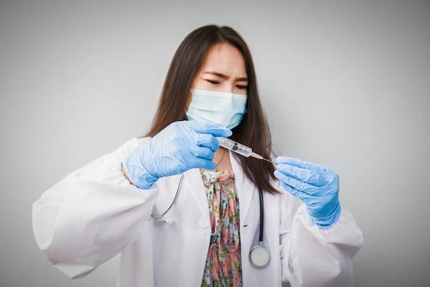 보호용 의료 마스크를 쓴 의사가 코로나바이러스 백신, 예방접종 및 예방접종을 주사할 준비를 하고 있다