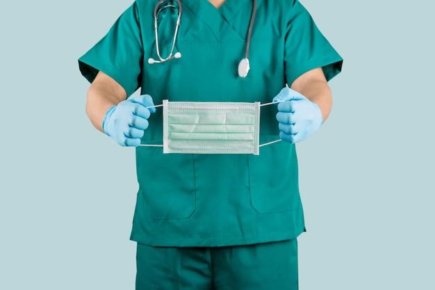 수술 가운을 입고 수술 마스크를 들고 의사