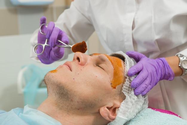 장갑을 끼고 의사가 성형 수술을 받기 전에 젊은 남성 환자의 얼굴을 치료합니다.