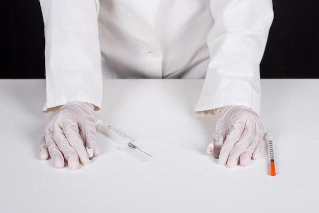 手術用手袋を着用し、ワクチンを手にする医師