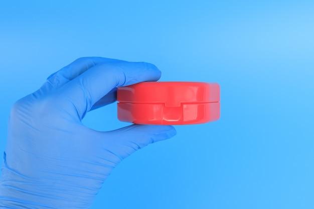 파란색 장갑을 든 의사가 치아 교정을위한 근기능 트레이너를위한 상자를 들고 있습니다.
