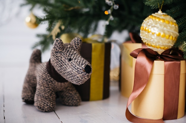 犬のおもちゃとクリスマスツリーの下の贈り物
