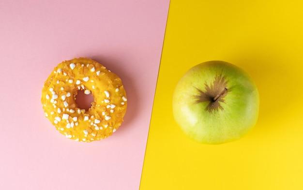 Пончик и яблоко на розовом и желтом фоне диеты концепции