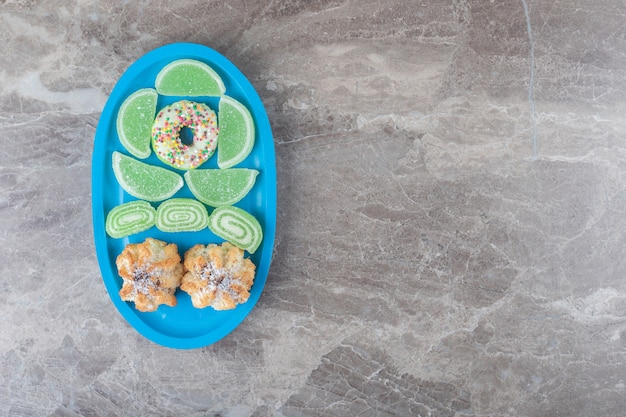 Пончик, печенье и мармелады на небольшом блюде на мраморной поверхности