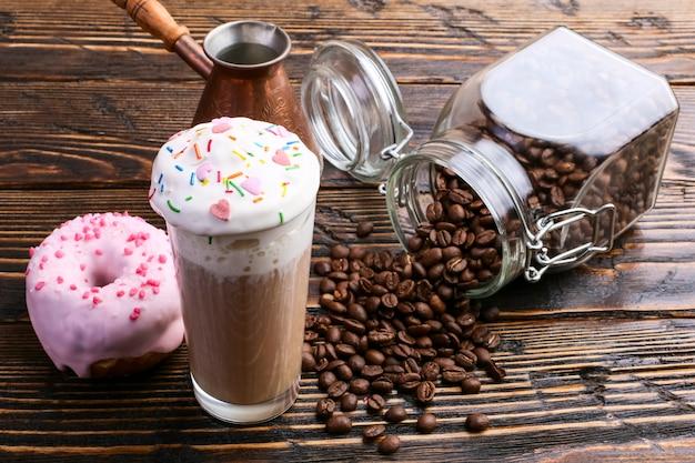 ピンクのアイシングとチョコレートパウダーが入ったドーナツ、高い泡と装飾が施されたカプチーノグラス。コーヒー缶と注ぐ穀物。