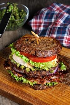 Двойной бутерброд из хлеба с кусочками бекона, авокадо, отварной куриной грудкой и помидорами