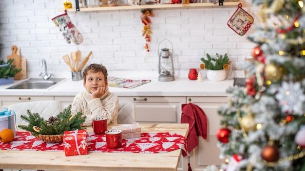 가벼운 스웨터를 입은 4 살짜리 꿈꾸는 아이가 식탁에 앉아 눈을 떴다. 배경에는 밝은 주방이 소나무 화환으로 장식되어 있습니다.