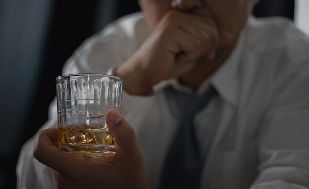 男のための飲み物。バーでウイスキーを飲む男のクロップドクローズアップ