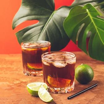 熱帯の緑の葉に対してガラスのゴブレットでラム酒またはコーラの角氷とジューシーなライムの飲み物
