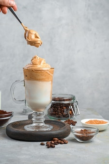 コーヒーの泡、牛乳、氷の入った飲み物、灰色の壁に写るスペースのある女性の手に、泡の入ったスプーンが置かれている。ダルゴナコーヒー。