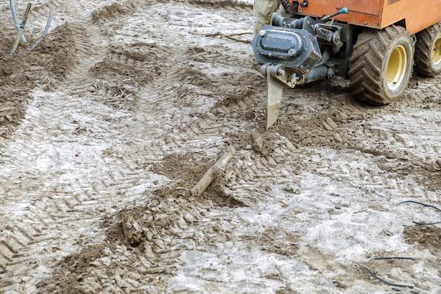 畑の水滴に設置された灌漑から滴り落ちる小さなトラクター
