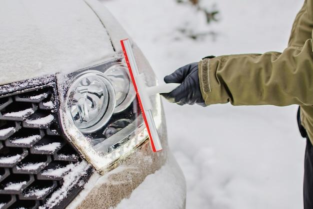 겨울 날에 자동차 조명을 청소하는 운전자. 추운 날씨에 눈이 덮여 차. 유리 청소 도구. 겨울에 눈에서 자동차의 헤드 라이트. 겨울 여행을 위해 차를 준비하십시오.