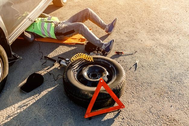 운전자 나 작업자가 길가에서 깨진 차를 수리합니다. 위에서 볼 수 있습니다. 남자는 차 아래