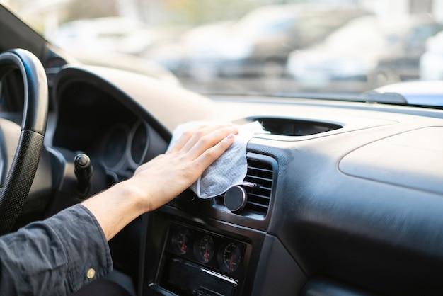 マイクロファイバーを持って車内を拭くドライバーの手