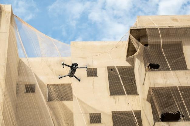 建設中の建物の隣を飛んでいるドローン。