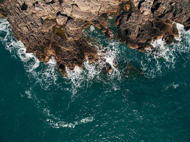 澄んだターコイズブルーの海の美しい岩のビーチのドローンショット