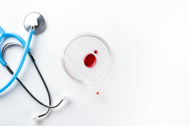 Капля крови в стеклянной чашке, стетоскоп.