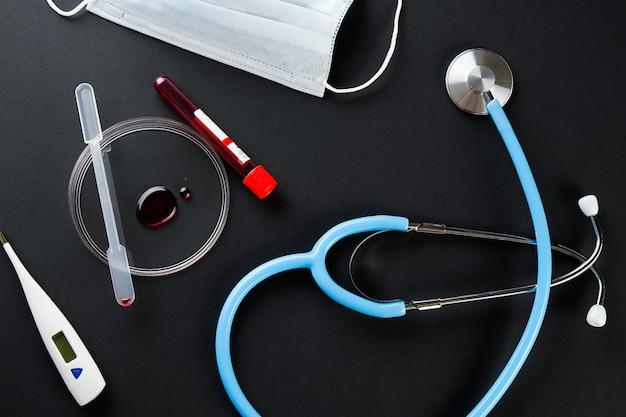 Капля крови в стеклянной чашке. пробирка с медицинским образцом для исследования, стетоскоп, медицинская маска.
