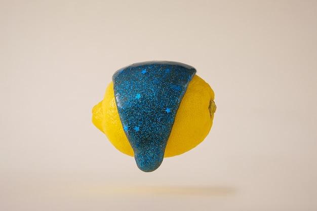 파란 슬라임 한 방울이 노란 레몬을 타고 흘러내립니다. 밝은 색상의 현대적인 재미있는 끈적 끈적한 점액.